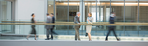 Man and woman standing near railing inside office building