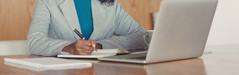 businesswoman writing in a notebook in front of her laptop.